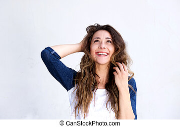 Laughing young woman with hand in hair looking up