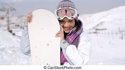Laughing young woman with her snowboard