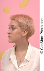Laughing young woman with short dyed blond hair and stars eye makeup. Over pink background. Looking to the different side.
