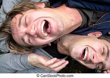Laughter. Two laughing young men close up.