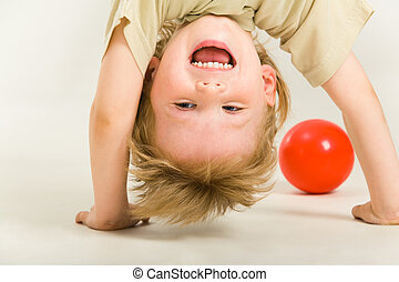 Laughter - View of boy�s head over heels on a white ...