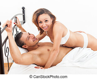 Laughting adult couple having sex on bed in bedroom interior