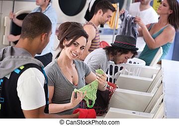 Laundromat Flirt - Woman holds panties and flirts with man...