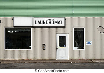 The front exterior and entrance to an old, run-down generic laundromat with sign.