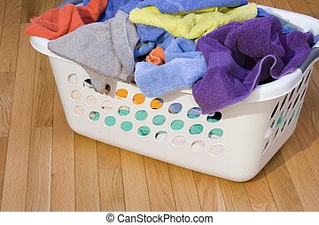 laundry basket full of clean towels on hardwood floor