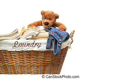 Laundry basket full of towels with teddy bear on white