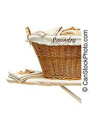 Laundry basket on ironing board against white