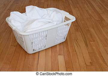 Laundry basket with white towels on wooden floor - Laundry ...