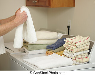 Laundry Day - Arms and hands of a male folding towels onto a...