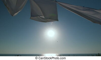 Laundry drying on clothesline against blue sky and sun