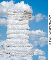 Fresh As A Summer Day - A stack of folded white towels and wash cloths outside against a bright blue sky with white puffy clouds.
