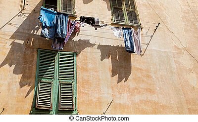 Laundry Hanging Over Stucco Wall and Green Shutter
