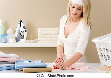 Laundry ironing - woman folding clothes, housework