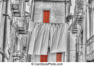 Laundry line with bed sheets in Bosa old town with selective...