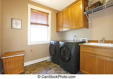 Laundry room with black appliances and nice cabinets