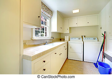 Laundry room with white old cabinets in large historical home.