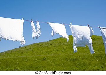 laundry - White clothes hanging on the line against blue sky...