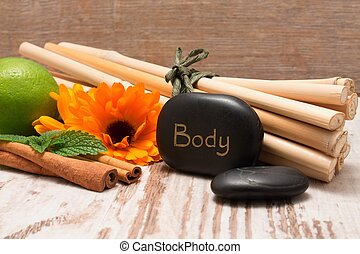 Lava stone with the inscription BODY, bamboo and marigold
