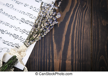 Lavender and paper music notes on old wooden background in vintage style.