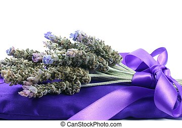 A bunch of fresh lavender tied with ribbon on lavender filled satin pillow