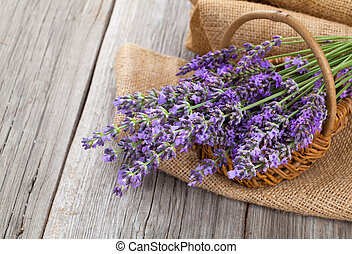 lavender flowers in a basket with burlap on the wooden backgrou