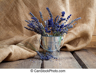 Lavender flowers in an iron bucket on a wooden background