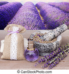 Lavender herbal water in a glass bottle with fresh and dry flowers on gray table