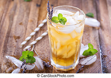 Lavender iced tea in tall glass with ice