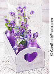 Lavender in bottles, decor provance style, wooden box and birdcage on crochet tablecloth