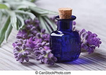 lavender oil in a blue glass bottle and flowers horizontal