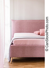 Lavender purple blanket on a pink bed with upholstered headboard in a beige bedroom interior with natural light