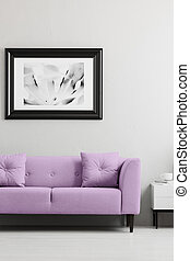 Lavender purple, trendy sofa and a framed photo mock-up in a gray living room interior with place for a lamp