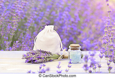 Lavender salt in the bottle with dropper on the gray wooden desk. Horizontal close-up. Skin care cream