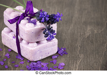 Lavender soap and bath salt on wooden background.