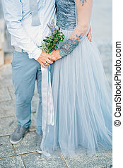 Lavender Wedding bouquet in hands of the bride in white-blue dre