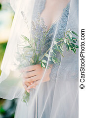 Lavender Wedding bouquet in hands of the bride under veil in pal