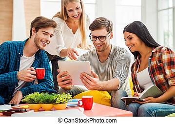 lavorando, creativo, progetto, insieme., gruppo, di, felice, giovani persone, guardando, tavoletta digitale, mentre, seduta, su, il, colorito, fagiolo, borse, in, ufficio