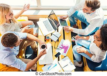 lavorare insieme, per, meglio, results., vista superiore, di, quattro, felice, giovani persone, lavorare insieme, mentre, seduta, a, il, scrivania legno, in, ufficio