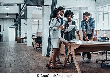 lavorativo, attraverso, un po', concepts., gruppo, di, giovane, persone affari, lavorare insieme, in, creativo, ufficio, mentre, standing, appresso, il, scrivania legno