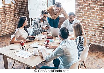 lavorativo, come, team., gruppo, di, sei, giovani persone, discutere, qualcosa, e, gesturing, mentre, sedere tavola, in, ufficio