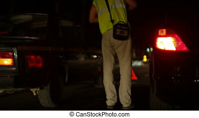 Law enforcement personnel investigate the scene of vehicle...