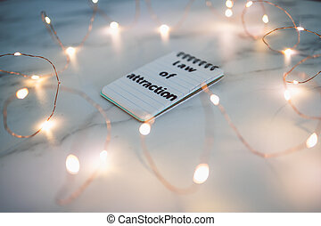 law of attraction, text on notepad surrounded by fairy lights