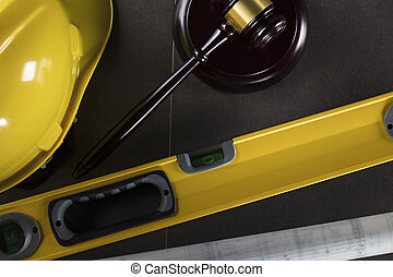 Construction law's symbols - helmet and gavel. Stone table and background.