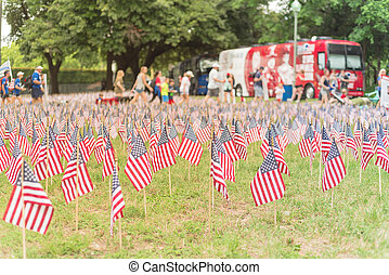 Lawn American flags with blurry row of people carry fallen soldiers banners parade