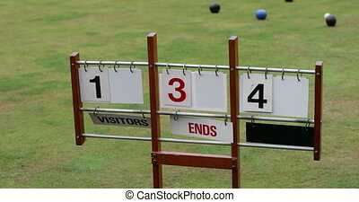 A close-up shot of a lawn bowling scoreboard on grass, showing double digits.