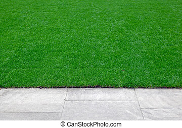 Edge of trimmed green grass field