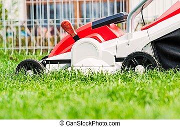 Lawn mower cutting green grass in garden.