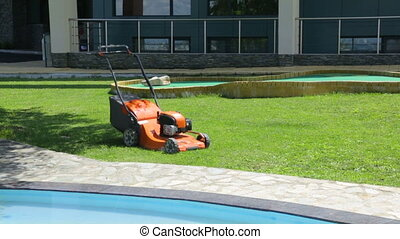 Lawn-mower on lawn by sunny day
