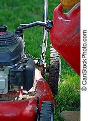 Lawn Mower - Pouring gas into lawn mower.