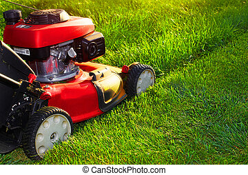Lawn mower. - Red lawn mower over green grass background.